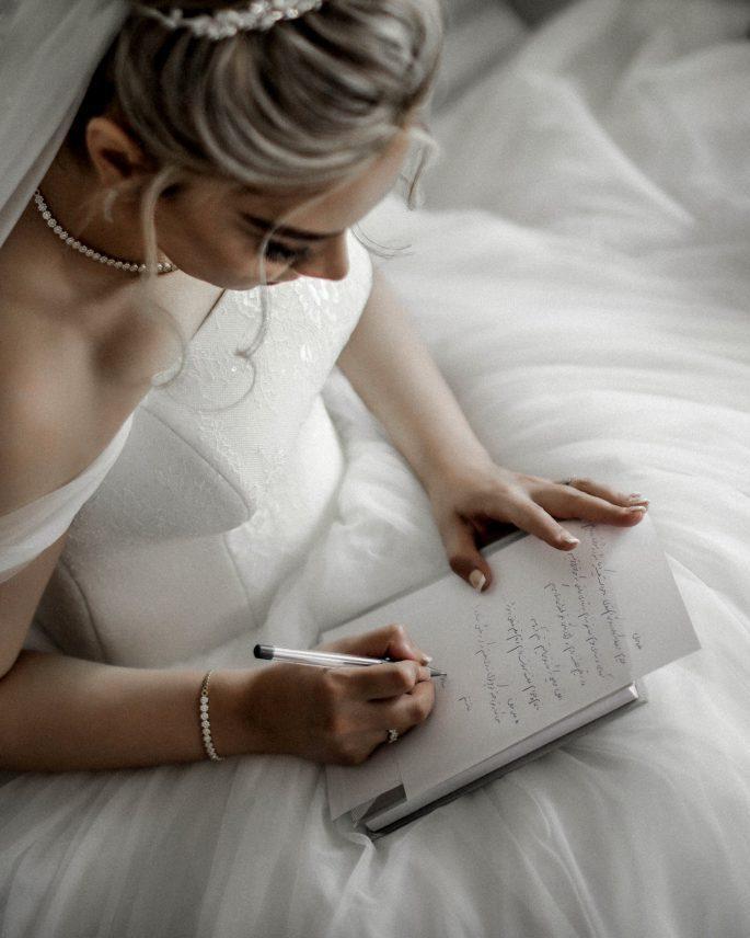 woman-in-white-wedding-dress-writing-on-book-3673462